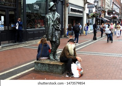 3rd August 2019, Dublin, Ireland. Man with long white beard sitting down in Earl Street Dublin city centre next to  a statue of James Joyce, sculpted by Marjorie Fitzgibbon and unveiled in 1990.
