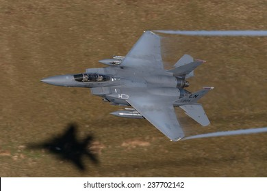 3rd December 2014. Wales, United Kingdom. McDonnell Douglas F-15 Eagle, practicing low flying techniques. A view looking down on to it with hillside as the background with shadow and vapor trail