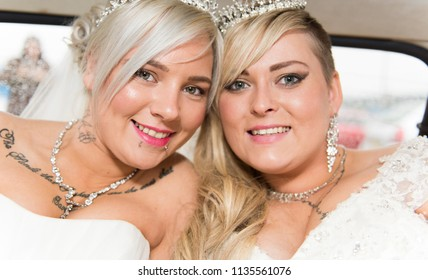 3rd - July - 2018 - Staffordshire, Beautiful gay, lesbian couple posing for pictures after the ceremony, holding each other in the wedding car