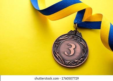 Bronzemedaille 3. Platz für einen Läufer in einem Wettkampf oder Rennen auf einem blau-gelben, wirbelfarbenen Band auf passendem gelbem Hintergrund mit Kopienraum