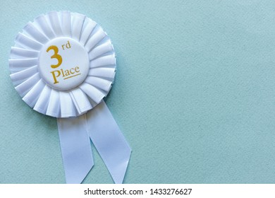3rd Place white ribbon rosette with gold text for a competition runner up winner on blue with copy space