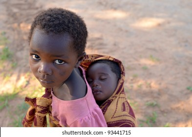 LUSAKA,ZAMBIA–DECEMBER 3:unidentified child with her brother .Many children are out of school to care for siblings when parents work in the fields,on December 3,2011 in Lusaka,Zambia