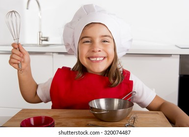 4 or 5 years old sweet little girl in red apron and cook hat playing chef learning cooking at home kitchen smiling happy