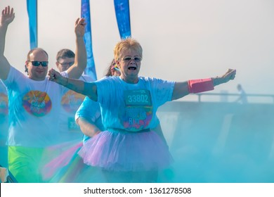 4 - 6 - 2019 - Two runners on a senior citizen woman in a tutu and a balding man behind her - hold their arms up as they run through colored powder at a Color Run race