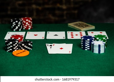 4 aces in Texas Hold-em on a green felt playing surface surrounded by betting chips and a big blind chip.  Bright foreground with a fast falloff to the back.  Room for copy in the foreground.