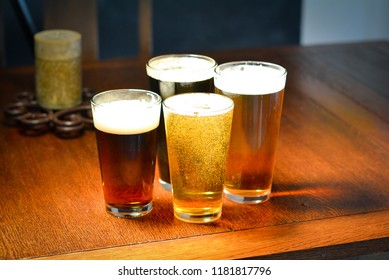 4 Beers on a wooden table.