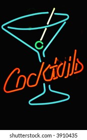 4 color neon sign in shape of cocktail glass with word cocktails in red