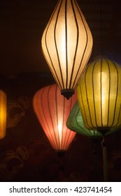 4 colorful Chinese paper lanterns hanging in the darkness. Varicolored textile lamps lighting at night