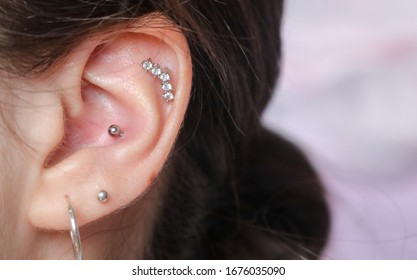 4 different piercings on an ear. Conch and helix piercings close up. Ear rings