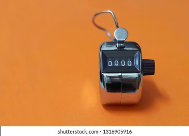 4 digits silver tally counter or hand counter on the orange background