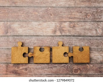 4 Four brown pieces of puzzle lie on wooden table background. empty copy space for inscription or objects.