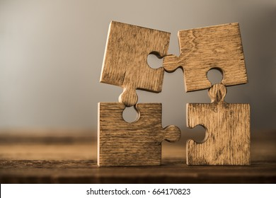 4 Four brown pieces of puzzle stand on wooden table isolated on gray or white background. empty copy space for inscription or objects. idea, sign, symbol, concept of connecting