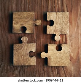 4 four wooden puzzle pieces. concept of connection people and brainstorming. isolated on wood background .