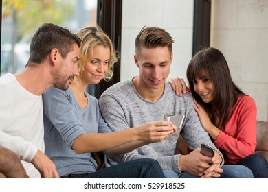 4 friends with smartphones on the sofa