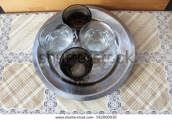 4 glasses filled with water, on a steel plate, top view.