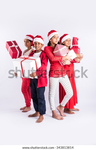 4 Indian Teenagers Holding Christmas Gifts Stock Photo (Edit