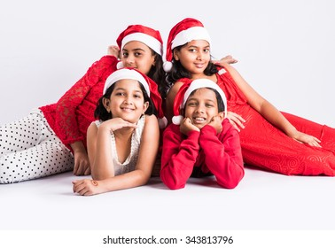 4 indian teenagers with red cloths and red santa hat, lying on white floor for photo, isolated on white background, close, indian kids and christmas, asian kids and christmas, legs folded, front view