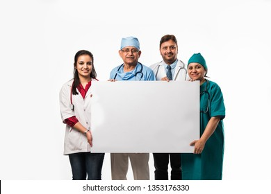 4 indian/asian doctors holding white blank board with copy space, standing isolated over white background