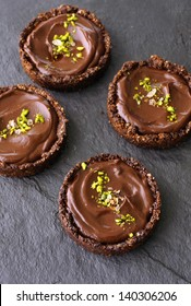 4 individual chocolate avocado pudding whole grain tarts on a black slate stone surface, sprinkled with pistachio and sea salt