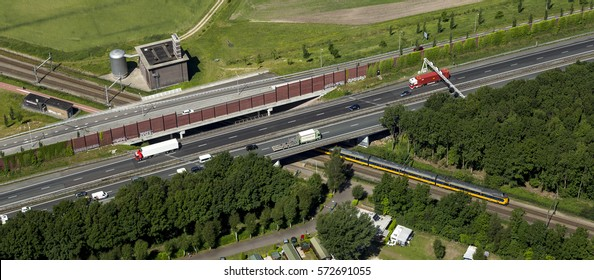 4 June 2015, Amersfoort, Netherlands. Aerial view of a blue and yellow Dutch train from NS crossing underneath a highway overpass.