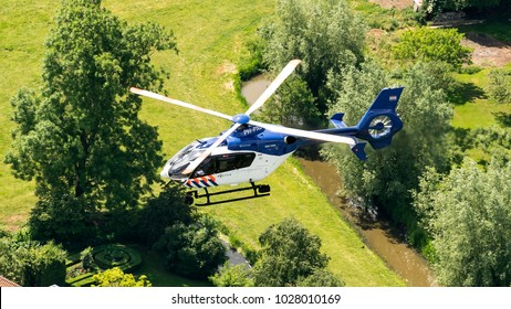 4 June 2017, Hilversum, Netherlands. Air-to-air aerial view of police chopper (Eurocopter EC-135) from the Dutch Politie above green trees and a gras.