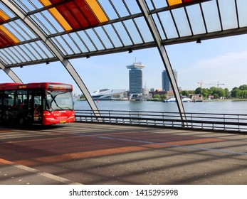 4 June 2019: Amsterdam, the Netherlands: view of the river ij from central station with the adam tower a ferry and bus on a sunny day.