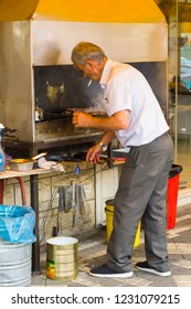 4 May 2018. A Druze Arab man cooking Halal meat on a restaurant barbeque with a stainless steel extractor chimney in the town of Buqata in the Golan Heights Israel.