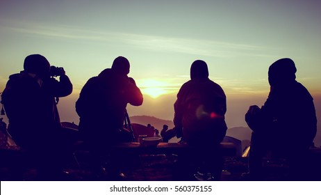 4 men having activities to sit and watch Photographing the sunrise Beautiful at the top of the mountain with cold weather, which is a good friendship, silhouette.