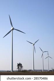 4 modern wind mills on a field