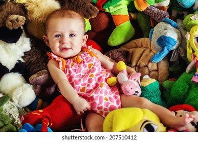 4 month old baby girl lying on a pile of stuffed toys -- image taken in Reno, Nevada, USA
