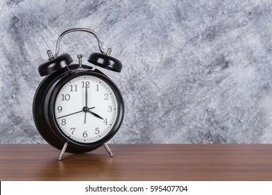 4 o'clock vintage clock on wood table and concrete wall background