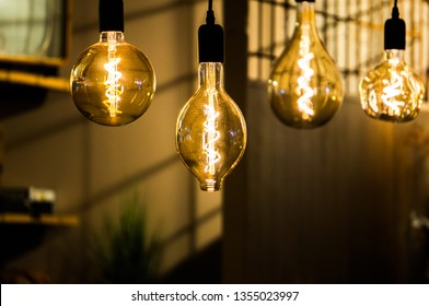 4 old fashioned spiral heated lamps of different shapes hanging in a restaurant with blurry background and book shelves