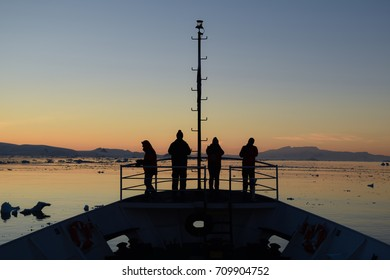 4 people looking at antarctic land and ocean at twilight
