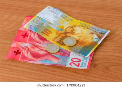 4 Polish zlote on 10 and 20 CHF Swiss franc banknotes in hand. - Shutterstock ID 1733851223
