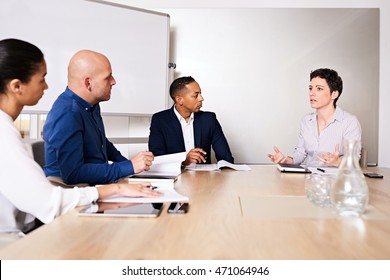 4 racially diverse entrepreneurs meeting with each other in a conference room to discuss the posibility of merging their businesses into one larger business with more market influence.