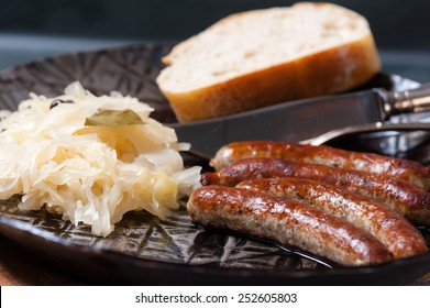 4 roasted Nuremberger Bratwurst/Sausages with Sauerkraut, Mustard and Bread in an iron Pan on a wooden board.