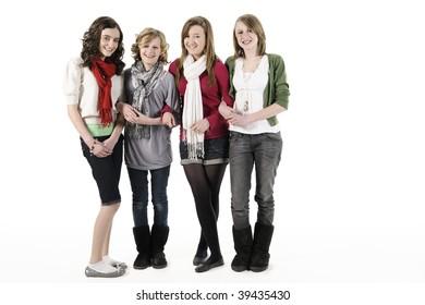 4 teenage girls standing on white smiling at camera