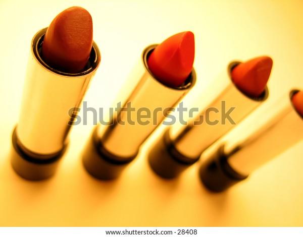 4 tubes of reddish toned lipstick on orange background. Light shadows. Focus on front tubes.