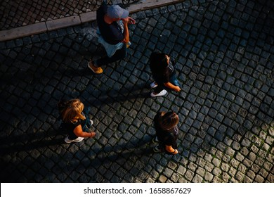 4 walkers seen from overhead on cobbled street and long morning shadows, 2019
