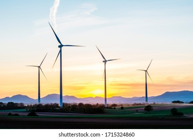 4 wind turbines stand in a small wind farm in the Rhine valley near Landau in front of the silhouette of the Palatinate Forest.