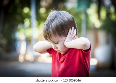 A 4 year old autistic child in a red shirt closing his ears with hands as if protecting from noise. Autism concept, Asperger syndrome, loud noise, scared little kid, parents divorce trauma.