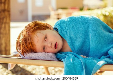 4 year old boy lying on a lounge chair, wrapped in a towel, not feeling well -- image taken outdoors in Reno, Nevada, USA