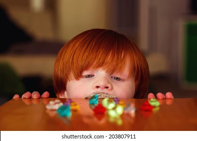 4 year old boy playing at a wooden table with toy gems -- image taken indoors in Reno, Nevada, USA
