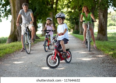 4 year old boy sitting on his bike in front of his family