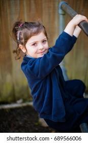 4 year old confident primary schoolgirl in school uniform looks forward to starting school