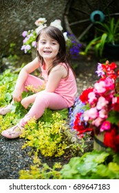 4 year old girl sits smiling and laughing in a pretty english country garden
