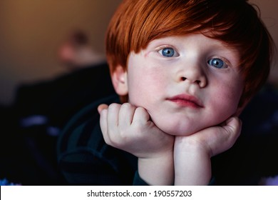 4 year old redheaded boy lying on a bed with his head resting in his hands--image taken indoors using natural light (Sparks, Nevada, USA)