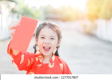 4 years old asian chinese child girl.Happy Little asian girl in chinese traditional dress smiling and holding red envelope.Happy chinese new year concept.