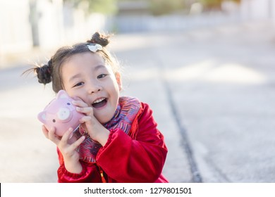 4 years old asian chinese child girl.Happy Little asian girl in chinese traditional dress smiling and holding holding pink piggy bank.Happy chinese new year concept.