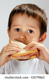 4 years old boy eating white bread sandwich (sandwich and studio lights reflected in eyes)